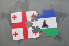 förbrylla med nationsflaggan av georgia och Lesotho på en världskarta Royaltyfri Fotografi