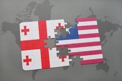 förbrylla med nationsflaggan av georgia och Liberia på en världskarta Royaltyfri Foto