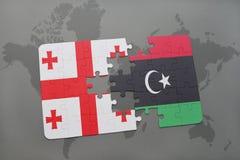 förbrylla med nationsflaggan av georgia och Libyen på en världskarta Royaltyfri Foto