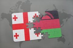 förbrylla med nationsflaggan av georgia och Malawi på en världskarta Arkivbilder