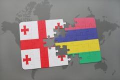 förbrylla med nationsflaggan av georgia och Mauritius på en världskarta Royaltyfri Bild