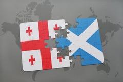 förbrylla med nationsflaggan av georgia och Skottland på en världskartabakgrund Arkivbilder