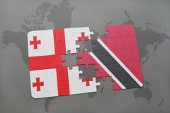 förbrylla med nationsflaggan av georgia och Trinidad och Tobago på en världskarta Arkivfoto
