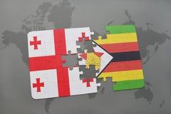 förbrylla med nationsflaggan av georgia och Zimbabwe på en världskarta Arkivfoton