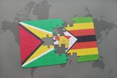 förbrylla med nationsflaggan av guyana och Zimbabwe på en världskarta Arkivfoton