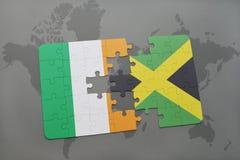 förbrylla med nationsflaggan av Irland och Jamaica på en världskarta Arkivfoton