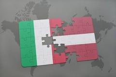förbrylla med nationsflaggan av Italien och Lettland på en världskartabakgrund Royaltyfri Fotografi