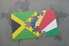 förbrylla med nationsflaggan av Jamaica och Seychellerna på en världskarta Arkivbilder