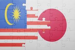 Förbrylla med nationsflaggan av Japan och Malaysia Arkivfoton