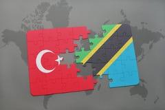 förbrylla med nationsflaggan av kalkon och Tanzania på en världskarta Arkivbilder