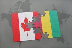 förbrylla med nationsflaggan av Kanada och guineaen på en världskartabakgrund Royaltyfri Fotografi