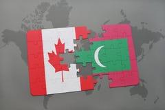 förbrylla med nationsflaggan av Kanada och Maldiverna på en världskartabakgrund Arkivbilder
