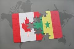 förbrylla med nationsflaggan av Kanada och Senegal på en världskartabakgrund Arkivbild