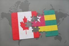 förbrylla med nationsflaggan av Kanada och Togo på en världskartabakgrund Arkivfoto