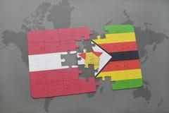 förbrylla med nationsflaggan av Lettland och Zimbabwe på en världskarta Fotografering för Bildbyråer