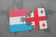 förbrylla med nationsflaggan av Luxemburg och georgia på en världskartabakgrund Arkivfoto
