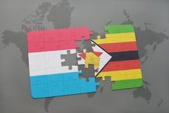 förbrylla med nationsflaggan av Luxemburg och Zimbabwe på en världskarta Arkivbild