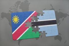 förbrylla med nationsflaggan av Namibia och Botswana på en världskarta Royaltyfria Bilder