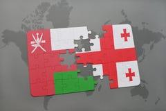 förbrylla med nationsflaggan av Oman och georgia på en världskartabakgrund Royaltyfria Bilder