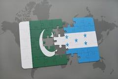 förbrylla med nationsflaggan av Pakistan och Honduras på en världskartabakgrund Royaltyfri Foto
