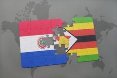 förbrylla med nationsflaggan av Paraguay och Zimbabwe på en världskarta Royaltyfri Foto