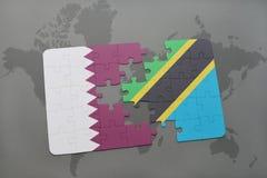 förbrylla med nationsflaggan av Qatar och Tanzania på en världskartabakgrund Arkivbilder