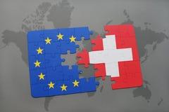Förbrylla med nationsflaggan av Schweiz och europeisk union på en världskartabakgrund arkivfoto
