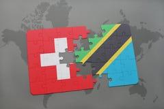 förbrylla med nationsflaggan av Schweiz och Tanzania på en världskartabakgrund Arkivfoto