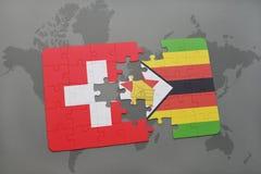 förbrylla med nationsflaggan av Schweiz och Zimbabwe på en världskartabakgrund Royaltyfria Bilder