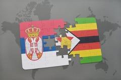 förbrylla med nationsflaggan av Serbien och Zimbabwe på en världskarta Arkivbild