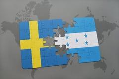 förbrylla med nationsflaggan av Sverige och Honduras på en världskartabakgrund Arkivbild