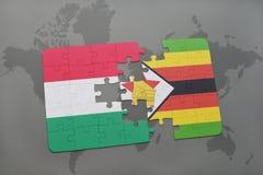 förbrylla med nationsflaggan av Ungern och Zimbabwe på en världskarta Royaltyfria Bilder