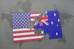 Förbrylla med nationsflaggan av USA och Australien på en världskartabakgrund Royaltyfri Bild