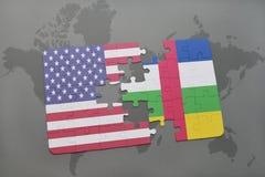 förbrylla med nationsflaggan av USA och Centralafrikanska republiken på en världskartabakgrund Arkivbild