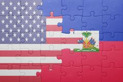 Förbrylla med nationsflaggan av USA och Haiti arkivfoton