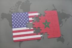 förbrylla med nationsflaggan av USA och Marocko på en världskartabakgrund Arkivbild