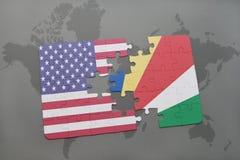 förbrylla med nationsflaggan av USA och Seychellerna på en världskartabakgrund Royaltyfri Bild
