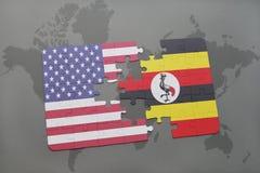 förbrylla med nationsflaggan av USA och Uganda på en världskartabakgrund Arkivbild