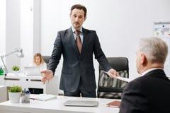 Förbryllad arbetsgivare som har konversation med kollegan i kontoret royaltyfri fotografi