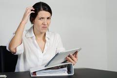 Förbryllad kvinna som skrapar hennes huvud arkivfoto