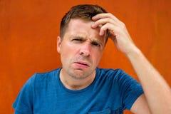 Förbryllad ung europeisk man i blått tänka för skjorta royaltyfri foto