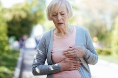 Förbryllat åldras kvinnan som har hjärtinfarkt utomhus arkivfoto