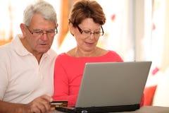 förbunden att göra internetbetalningpensionären Arkivfoton