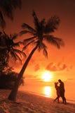 Förbunden att kyssa på stranden på solnedgången, Maldiverna Arkivfoton