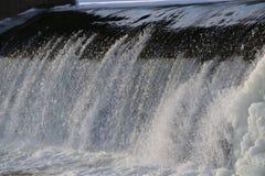 Fördämning vattenfall strömmen av floden faller från fördämningen i vintern iskall fördämning med en stark ström av floden skinan arkivfoto