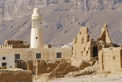 Fördärva av en gammal gyttjategelstenfästning och en bymoské, nära staden av Seiyun, Yemen arkivfoton