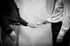 Fördärvad affärsman eller politiker som betalar en Hryvnia sedelmuta till en man som accepterar korruption Royaltyfri Foto