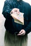 Fördärvad affärsman eller politiker som erbjuder en Hryvnia sedelmuta Royaltyfri Bild