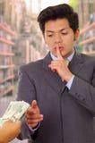 Fördärvad ung affärsman som accepterar några pengar från en skurk royaltyfria bilder
