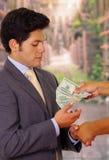 Fördärvad ung affärsman som accepterar några pengar från en skurk arkivbild